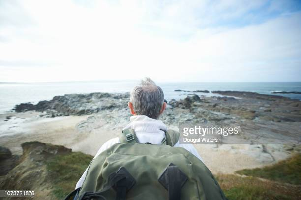 senior hiker looking out to sea from clifftop viewpoint. - explore stock photos and pictures