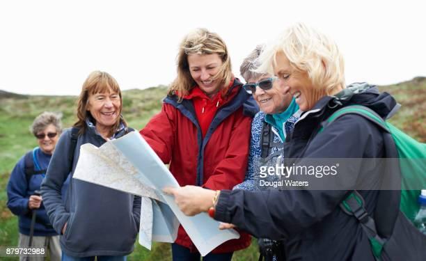 senior hikers checking map. - fünf personen stock-fotos und bilder