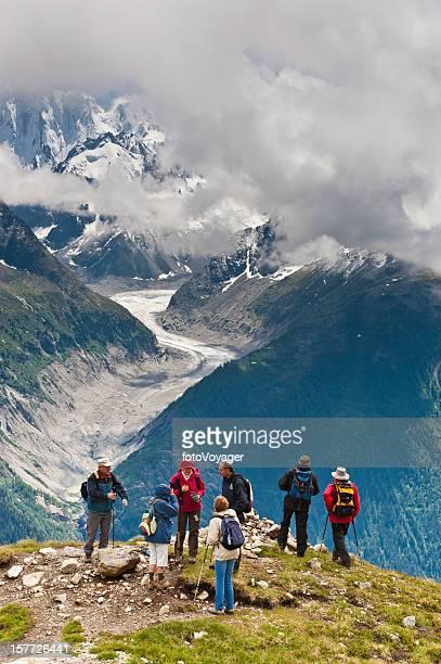 Senior hikers on mountain overlooking glacier Alps