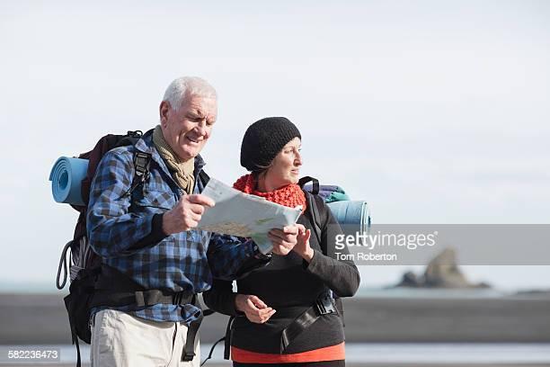 Senior hikers reading map on beach