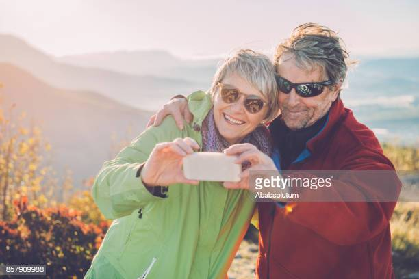 Senior Hikers Taking Selfie  at Autumnal Dawn in Southern Julian Alps, Europe