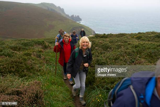 senior hiking group walking along coastal path and laughing. - buitensport stockfoto's en -beelden