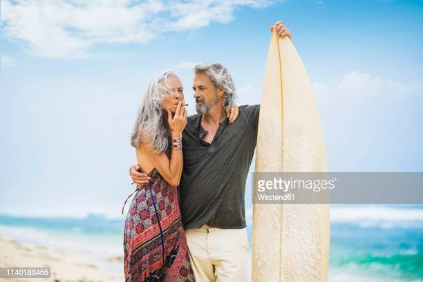senior hippie couple with surfboard on the beach - hashish photos et images de collection