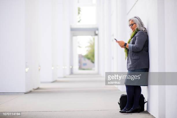 senior hispanic businesswoman on the phone - white hair stock pictures, royalty-free photos & images