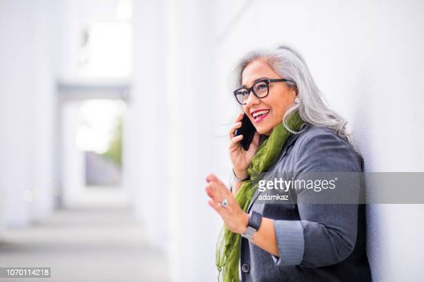 senior hispanic businesswoman on the phone - mexican business women stock photos and pictures