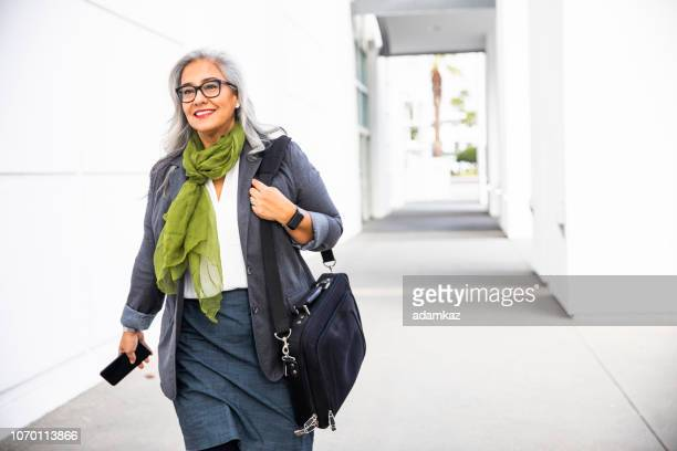 senior hispanic businesswoman walking down hallway - businesswoman stock pictures, royalty-free photos & images