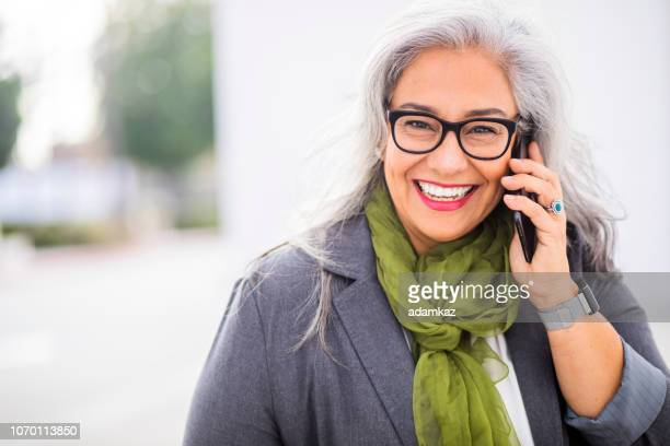 Senior hispanic businesswoman Walking with phone