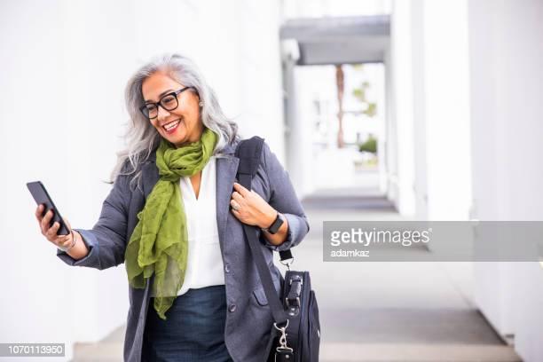 Senior hispanic businesswoman Walking with phone
