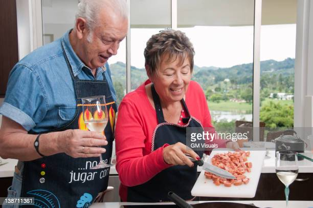 senior hispanic couple cooking together in kitchen - putting stock pictures, royalty-free photos & images