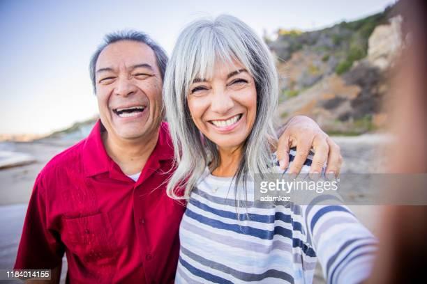 senior hispanic paar het nemen van selfie op het strand - medicare stockfoto's en -beelden