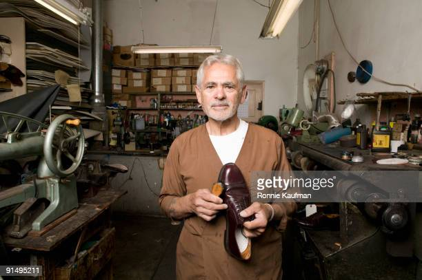 senior hispanic male cobbler holding shoe - shoemaker stock photos and pictures