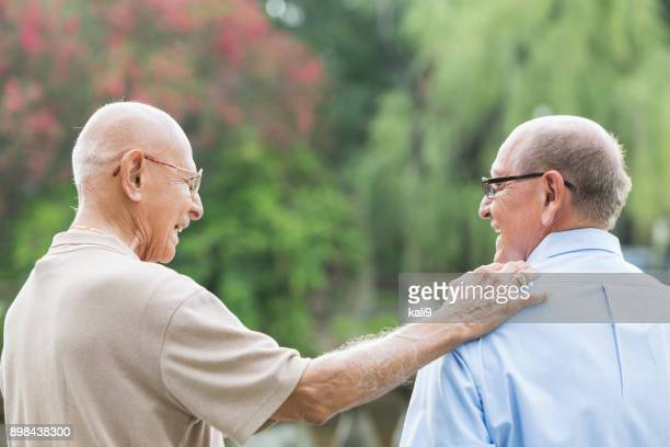 senior hispanic man and his father, 90 plus years - hand on shoulder stock pictures, royalty-free photos & images