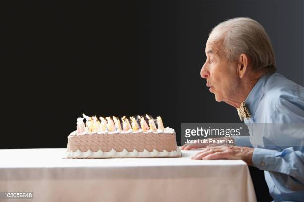 senior hispanic man blowing out birthday candles - soplar fotografías e imágenes de stock