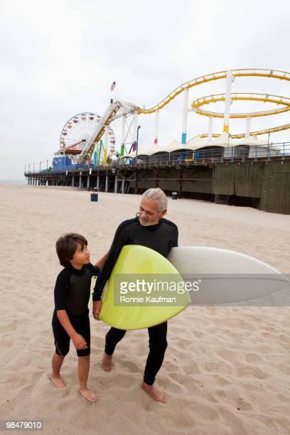 Senior Hispanic man carrying surfboards with grandson