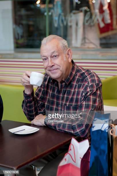 Senior Hispanic man drinking coffee in cafe