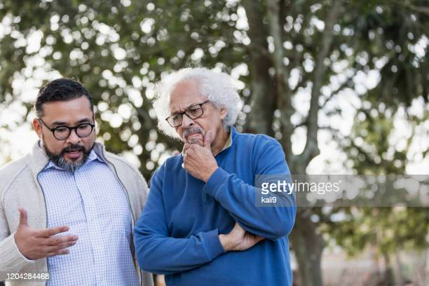 senior hispanic man frowning as adult son talks - stubborn stock pictures, royalty-free photos & images