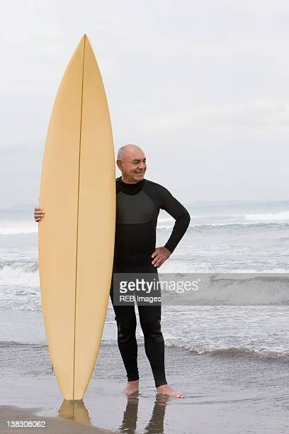 Senior Hispanic man holding surfboard on beach