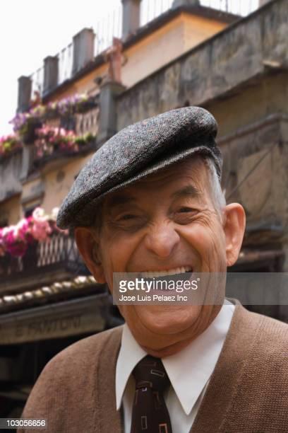 Senior Hispanic man in cap, smiling