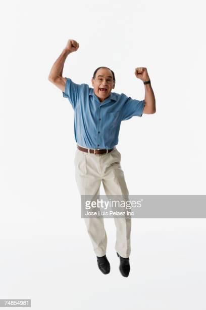 senior hispanic man jumping - one senior man only stock pictures, royalty-free photos & images