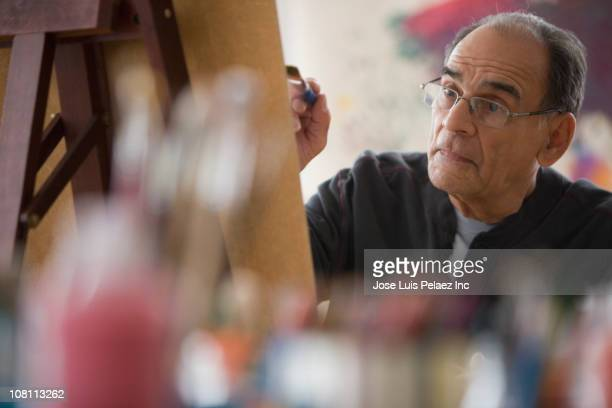 Senior Hispanic man painting on easel