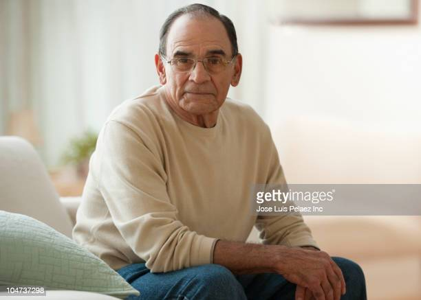 senior hispanic man sitting in living room - west new york new jersey - fotografias e filmes do acervo