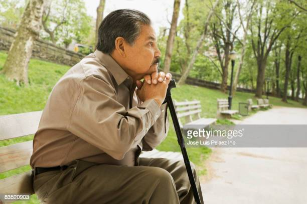 senior hispanic man sitting on park bench - leaning disability stock pictures, royalty-free photos & images