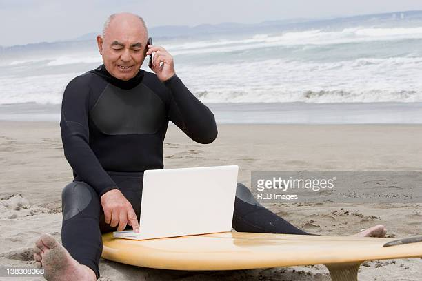 Senior Hispanic man sitting on surfboard using laptop and talking on cell phone
