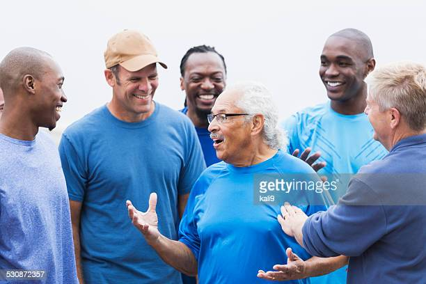 senior hispanic man talking with group of friends - african american man helping elderly stock pictures, royalty-free photos & images