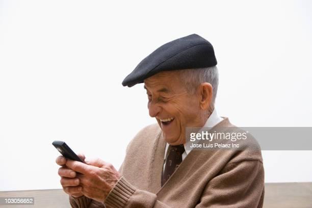 senior, hispanic man text messaging on cell phone - solo un uomo foto e immagini stock
