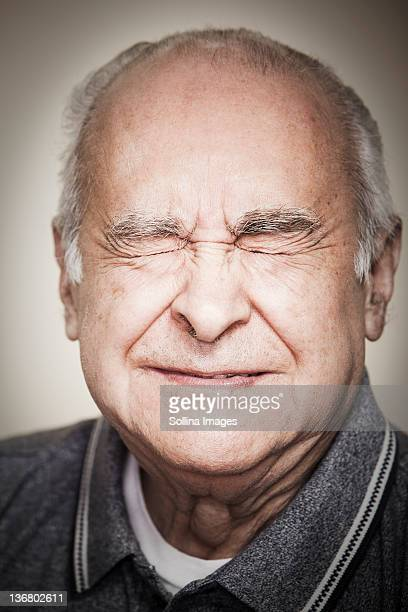 senior hispanic man with eyes closed - grimassen stockfoto's en -beelden