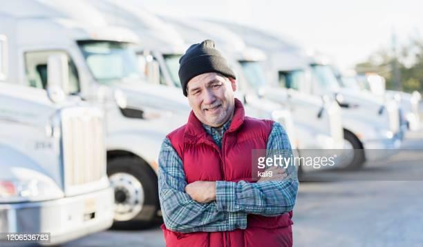 senior hispanic mann mit flotte von semi-trucks - ärmellos stock-fotos und bilder