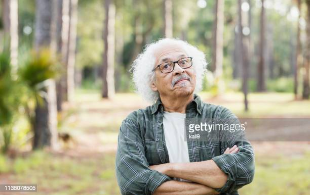 senior hispanic man with white hair and eyeglasses - stubborn stock pictures, royalty-free photos & images