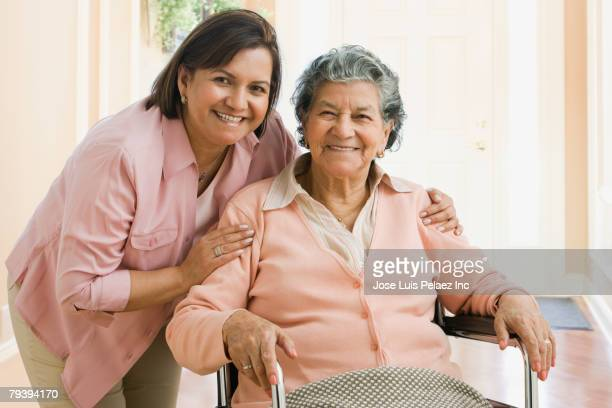 senior hispanic woman and adult daughter hugging - leaning disability stock pictures, royalty-free photos & images