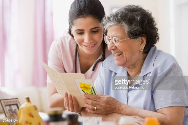 senior hispanic woman and nurse looking at greeting card - birthday card stock pictures, royalty-free photos & images