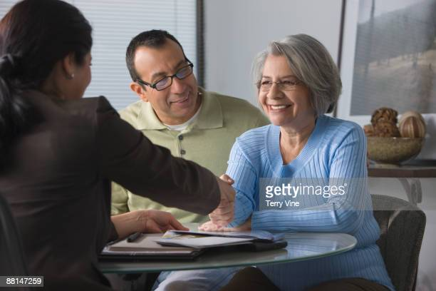 Senior Hispanic woman and son taking with saleswoman