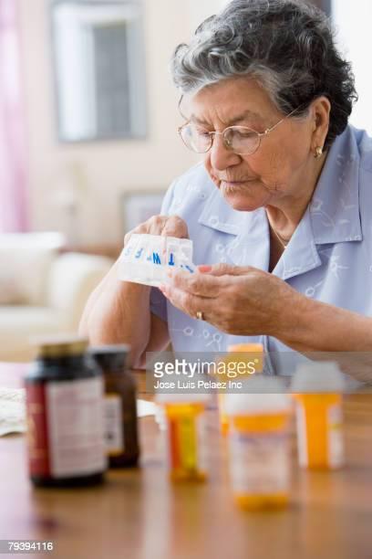Senior Hispanic woman filing pill organizer