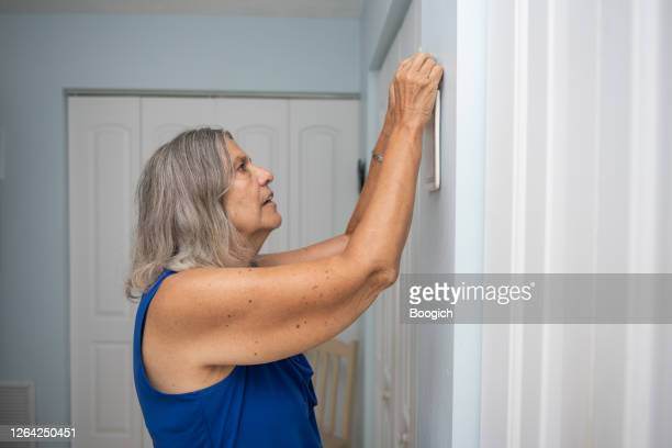 Senior Hispanic Woman Hanging Up Wall Decor In Home Interior In Orlando Florida High Res Stock Photo Getty Images