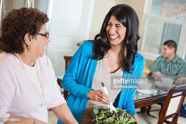 Senior Hispanic woman helping her daughter prepare dinner for family