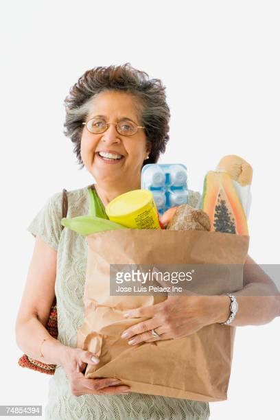 Senior Hispanic woman holding bag of groceries