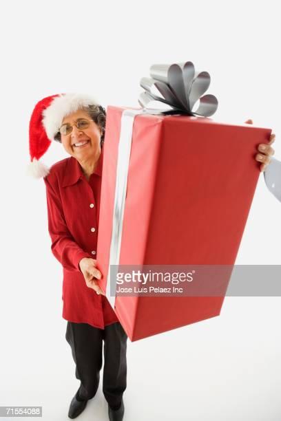Senior Hispanic woman holding large gift