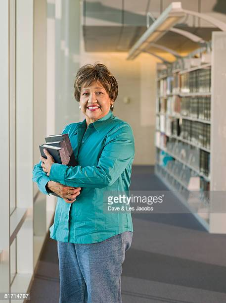 Senior Hispanic woman holding library books