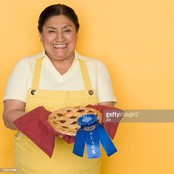 Senior Hispanic woman holding pie with first place ribbon