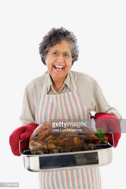 Senior Hispanic woman holding roasted turkey in pan