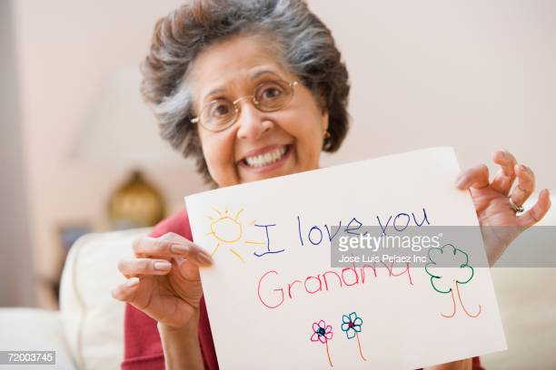 senior hispanic woman holding up child's drawing - i love you stock pictures, royalty-free photos & images
