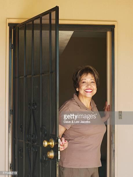 Senior Hispanic woman in open doorway