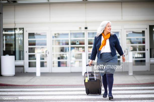 senior hispanic woman leaving the airport - fat old lady stock photos and pictures