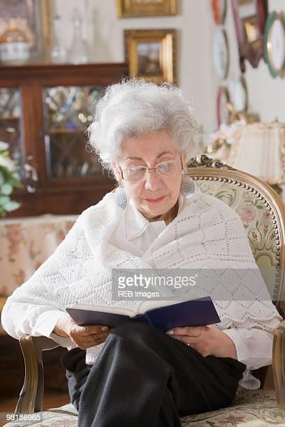 senior hispanic woman reading book - shawl stock pictures, royalty-free photos & images