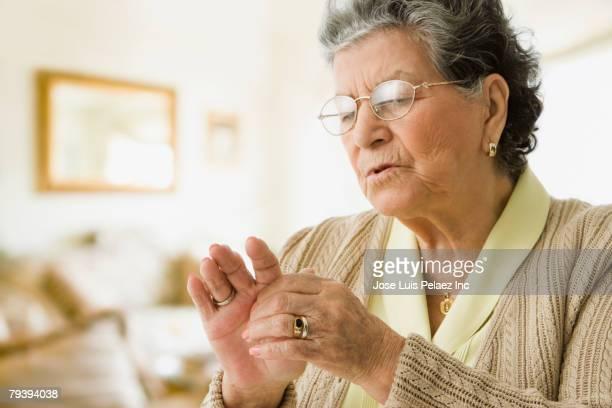 Senior Hispanic woman rubbing hand