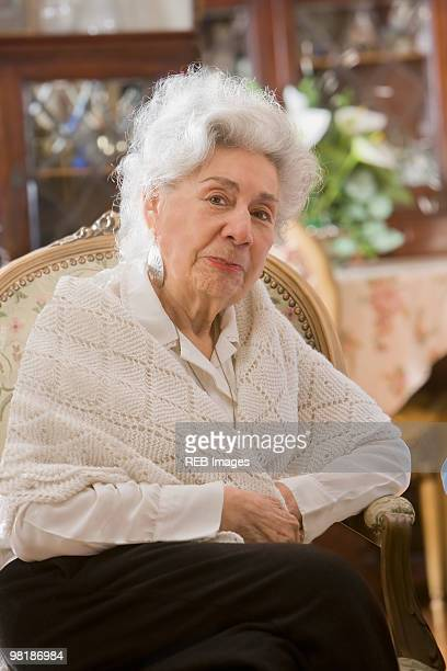 senior hispanic woman sitting in chair - shawl stock pictures, royalty-free photos & images