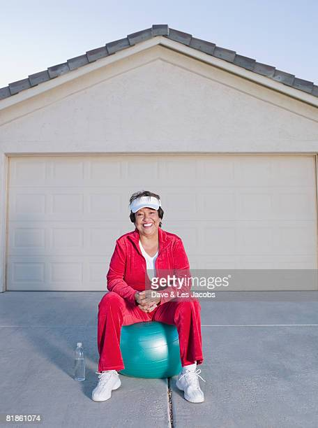 Senior Hispanic woman sitting on exercise ball